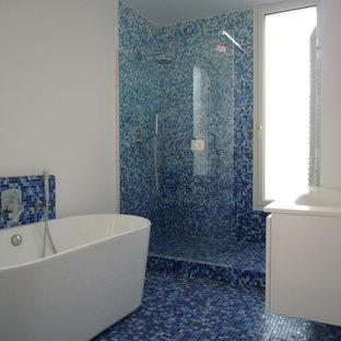 パリの中サイズのコンテンポラリースタイルのおしゃれなマスターバスルーム (フラットパネル扉のキャビネット、白いキャビネット、置き型浴槽、段差なし、マルチカラーのタイル、モザイクタイル、白い壁、モザイクタイル、一体型シンク、珪岩の洗面台) の写真