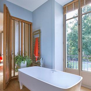 Exemple d'une grand salle de bain principale tendance avec une baignoire indépendante, un mur bleu, un sol en bois clair et un sol beige.