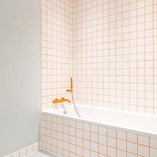 Exemple d'une salle de bain tendance avec une baignoire posée, un carrelage orange, un mur gris et un sol gris.