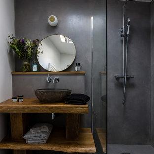Cette image montre une petit salle de bain principale design avec une douche à l'italienne, un mur gris, béton au sol, un plan de toilette en bois, un sol gris, un placard sans porte, des portes de placard en bois brun, une vasque, aucune cabine et un plan de toilette marron.