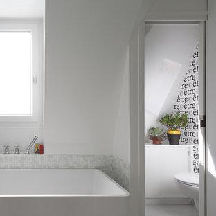 Inspiration pour une petite douche en alcôve principale design avec un placard à porte affleurante, des portes de placard blanches, une baignoire indépendante, un WC séparé, un carrelage blanc, carrelage en mosaïque, un mur blanc, un sol en carrelage de céramique et un lavabo suspendu.