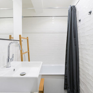 Photo of a small scandinavian master bathroom in Paris with a drop-in tub, a shower/bathtub combo, subway tile, white walls, ceramic floors, a vessel sink, open cabinets, white cabinets, white tile, solid surface benchtops, black floor, a shower curtain and white benchtops.