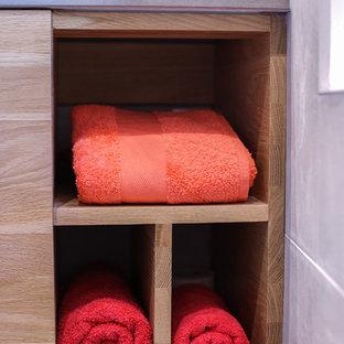 Ejemplo de cuarto de baño con ducha, contemporáneo, pequeño, con armarios con rebordes decorativos, puertas de armario de madera clara, sanitario de pared, baldosas y/o azulejos grises, baldosas y/o azulejos de porcelana, paredes grises, suelo de baldosas de porcelana, lavabo bajoencimera, encimera de piedra caliza, suelo gris, ducha con puerta con bisagras y ducha esquinera
