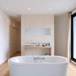 Mittelgroßes Modernes Badezimmer En Suite mit Aufsatzwaschbecken, freistehender Badewanne, beiger Wandfarbe, hellem Holzboden, Waschtisch aus Holz und beiger Waschtischplatte in Bordeaux