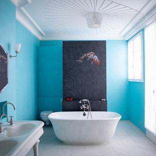 Foto de cuarto de baño principal, tradicional renovado, con bañera exenta, sanitario de pared, baldosas y/o azulejos negros, baldosas y/o azulejos en mosaico, paredes azules, lavabo con pedestal y suelo blanco