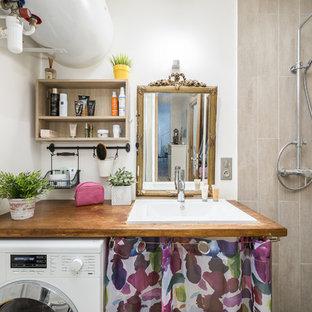 Exemple d'une salle de bain éclectique avec un carrelage beige, un mur blanc, un lavabo posé, un plan de toilette en bois, aucune cabine et un plan de toilette marron.