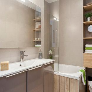 Réalisation d'une petite salle de bain principale design avec un lavabo intégré, un placard à porte plane, des portes de placard grises, un combiné douche/baignoire, un carrelage gris, un mur beige et un bain japonais.