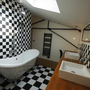 Inspiration pour une salle de bain principale design de taille moyenne avec une baignoire indépendante, un combiné douche/baignoire, un carrelage noir et blanc, des carreaux de céramique, un mur blanc, un sol en carrelage de céramique, une vasque et un plan de toilette en bois.