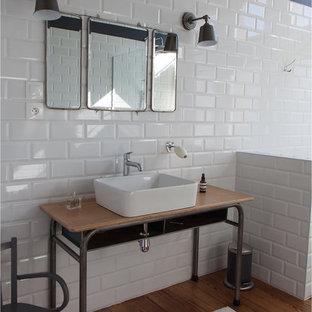 Idée de décoration pour une salle de bain principale urbaine de taille moyenne avec une vasque, un plan de toilette en bois, un carrelage blanc, un carrelage métro, un mur noir, un sol en bois brun et un plan de toilette marron.