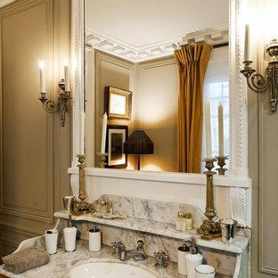 Idée de décoration pour une grande salle de bain principale victorienne avec des portes de placard en bois brun, un mur beige, un lavabo encastré et un plan de toilette en marbre.