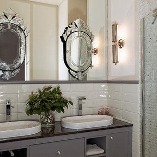 Réalisation d'une salle de bain tradition avec un lavabo posé, des portes de placard grises, un mur blanc et un plan de toilette en verre.