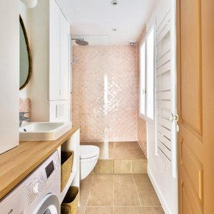 Aménagement d'une salle d'eau romantique de taille moyenne avec une douche à l'italienne, aucune cabine, meuble simple vasque, un placard à porte plane, des portes de placard blanches, un WC suspendu, un carrelage rose, un mur blanc, un plan vasque, un plan de toilette en bois, un sol beige, buanderie et meuble-lavabo encastré.