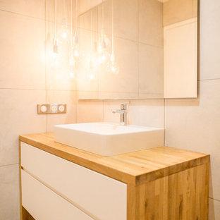 Immagine di una stanza da bagno nordica di medie dimensioni con ante lisce, ante bianche, piastrelle beige, pareti beige, lavabo da incasso, top in legno, pavimento beige e top marrone