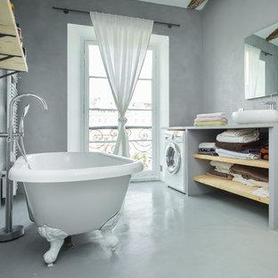 Réalisation d'une salle de bain principale tradition avec une vasque, un placard sans porte, des portes de placard en bois clair, une baignoire sur pieds et un mur gris.