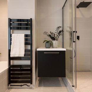 Idée de décoration pour une douche en alcôve principale design de taille moyenne avec des portes de placard noires, des carreaux de céramique, un plan de toilette en surface solide, un plan de toilette blanc, une cabine de douche à porte coulissante, un placard à porte plane, une baignoire posée, un carrelage gris et un sol gris.