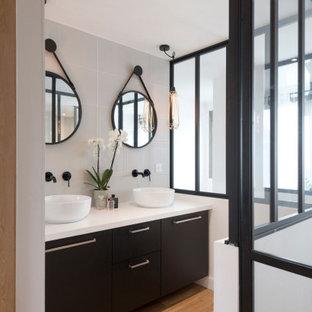 Idées déco pour une salle de bain principale contemporaine de taille moyenne avec des portes de placard noires, des carreaux de céramique, un plan de toilette en surface solide, un plan de toilette blanc, un mur blanc, un placard à porte plane, un carrelage gris, un sol en bois brun, une vasque et un sol marron.