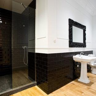 Exemple d'une grand salle de bain tendance avec un lavabo de ferme, un carrelage noir, un mur blanc, un sol en bois clair, un WC à poser et un carrelage métro.