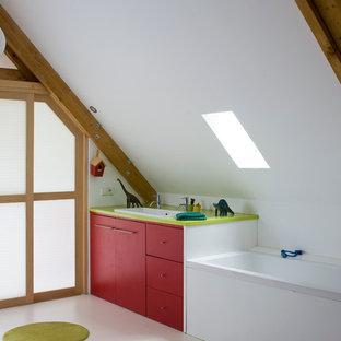 Exemple d'une salle de bain tendance de taille moyenne pour enfant avec un lavabo posé, un placard à porte plane, des portes de placard rouges, une baignoire posée et un mur blanc.