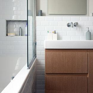 Inspiration pour une salle de bain principale design de taille moyenne avec des portes de placard en bois brun, une baignoire posée, un carrelage blanc, un mur blanc, un carrelage métro et un plan vasque.