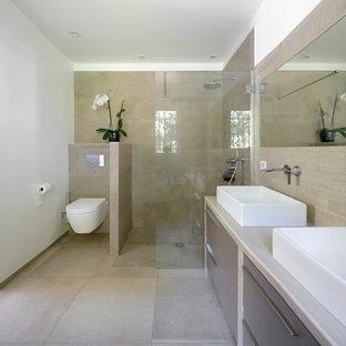 Exemple d'une grand salle d'eau tendance avec une vasque, un placard à porte plane, des portes de placard grises, un WC suspendu, un carrelage beige, un mur blanc, une douche à l'italienne et un sol beige.