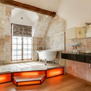 Ispirazione per una grande stanza da bagno padronale eclettica con vasca con piedi a zampa di leone, doccia alcova, piastrelle beige, pareti beige, pavimento in legno massello medio e lavabo integrato