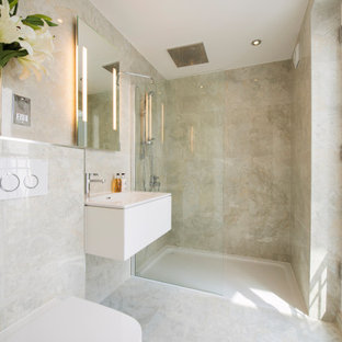 Design ideas for a medium sized contemporary shower room bathroom in London with flat-panel cabinets, white cabinets, an alcove shower, a wall mounted toilet, beige walls, an integrated sink, beige floors and white worktops.