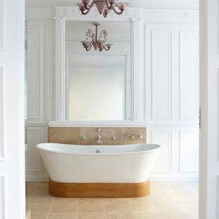Aménagement d'une grande salle de bain principale classique avec une baignoire indépendante, un mur blanc et un sol en travertin.