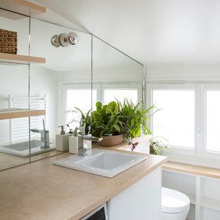 Inredning av ett modernt beige beige badrum, med öppna hyllor, spegel istället för kakel, ett nedsänkt handfat, vitt golv, vita skåp och träbänkskiva