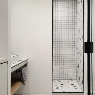 Exempel på ett mellanstort eklektiskt badrum med dusch, med vita skåp, en dusch i en alkov, vit kakel, vita väggar, klinkergolv i keramik, ett avlångt handfat, bänkskiva i glas, flerfärgat golv och med dusch som är öppen