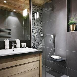 Inredning av ett modernt mellanstort badrum med dusch, med släta luckor, skåp i ljust trä, svart kakel, svarta väggar, ett nedsänkt handfat, en kantlös dusch, keramikplattor och klinkergolv i keramik