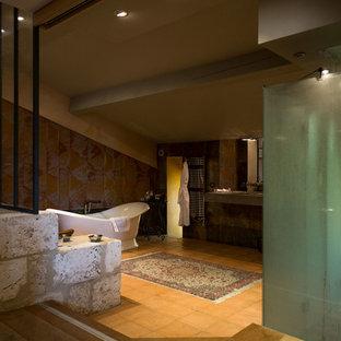 Imagen de cuarto de baño con ducha, bohemio, grande, con armarios tipo vitrina, puertas de armario de madera clara, bañera encastrada, ducha doble, paredes beige, suelo de baldosas de terracota, lavabo integrado, encimera de cemento, ducha con puerta con bisagras, encimeras grises y suelo naranja