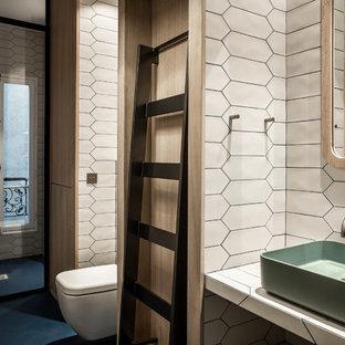 Immagine di una grande stanza da bagno con doccia design con doccia alcova, WC sospeso, piastrelle bianche, piastrelle in ceramica, pareti bianche, pavimento in cemento, lavabo rettangolare, top piastrellato, pavimento blu e porta doccia a battente