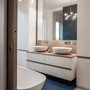 Idee per una grande stanza da bagno padronale design con ante bianche, vasca freestanding, pavimento in cemento, top in legno, pavimento blu, ante lisce, pareti bianche, lavabo a bacinella e top beige