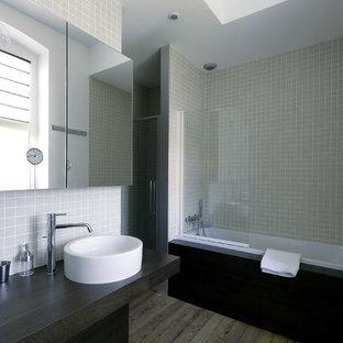 Inspiration pour une grand salle de bain principale design avec des portes de placard en bois sombre, une baignoire posée, un combiné douche/baignoire, un carrelage beige, des carreaux de céramique, un sol en bois brun, une vasque, un plan de toilette en bois et un plan de toilette noir.