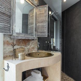 Exempel på ett lantligt badrum med dusch, med en hörndusch, öppna hyllor, svarta väggar, klinkergolv i småsten och ett undermonterad handfat
