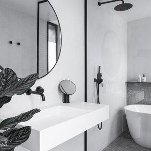 Exemple d'une salle de bain tendance avec une baignoire indépendante, un mur blanc, un lavabo suspendu et un sol gris.