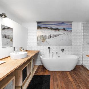 Cette photo montre une salle de bain principale scandinave avec un placard sans porte, une baignoire indépendante, un carrelage blanc, un carrelage métro, un mur blanc, un sol en bois brun, une cabine de douche à porte battante, une douche d'angle, une vasque, un plan de toilette en bois, un sol marron et un plan de toilette beige.