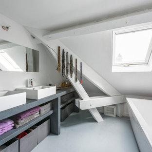 Cette image montre une salle de bain principale design de taille moyenne avec un placard sans porte, des portes de placard grises, une baignoire posée, des carreaux de céramique, un mur blanc, béton au sol, une vasque et un plan de toilette en béton.
