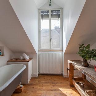 На фото: ванная комната в стиле фьюжн с ванной на ножках, белыми стенами, паркетным полом среднего тона, коричневым полом, нишей и сводчатым потолком с