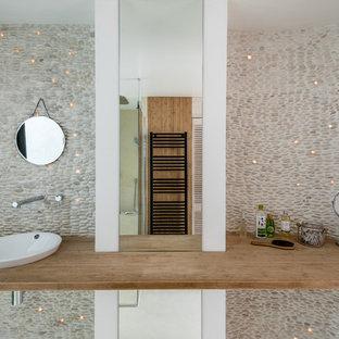 Imagen de cuarto de baño con ducha, marinero, de tamaño medio, con baldosas y/o azulejos beige, suelo de baldosas tipo guijarro, paredes blancas, lavabo bajoencimera y encimera de madera