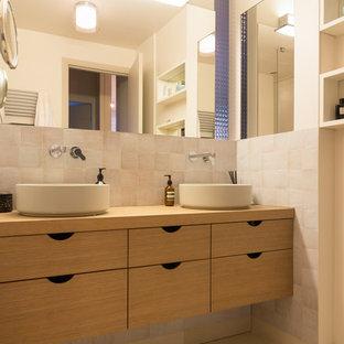 Mittelgroßes Modernes Badezimmer mit hellen Holzschränken, weißen Fliesen, Terrakottafliesen, beiger Wandfarbe, Kalkstein, Einbauwaschbecken, Waschtisch aus Holz und beigem Boden in Paris