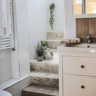 Réalisation d'une salle de bain tradition avec un placard à porte plane, des portes de placard blanches, un carrelage marron, un carrelage blanc, un lavabo intégré, un sol marron et un plan de toilette blanc.