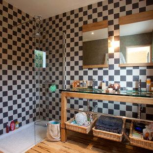 Réalisation d'une salle d'eau design de taille moyenne avec un placard sans porte, des portes de placard en bois clair, un plan de toilette en verre, une douche d'angle, un mur multicolore, un sol en bois brun, un carrelage noir et blanc et un lavabo intégré.