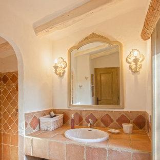 Diseño de cuarto de baño con ducha, campestre, de tamaño medio, con baldosas y/o azulejos de terracota, paredes blancas, lavabo encastrado, ducha empotrada y baldosas y/o azulejos marrones