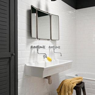 Cette photo montre une salle de bain industrielle avec un carrelage blanc, un carrelage métro, une grande vasque, une baignoire posée et un mur blanc.