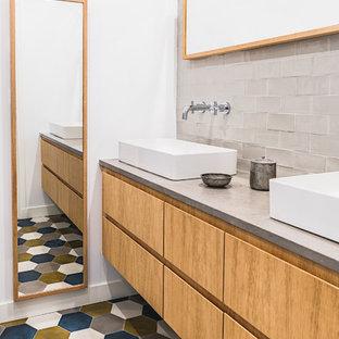 Réalisation d'une salle de bain design avec un placard à porte plane, des portes de placard en bois brun, un carrelage gris, un carrelage métro, un mur blanc, une vasque, un plan de toilette en béton, un sol multicolore et un plan de toilette gris.
