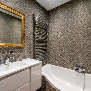 Exemple d'une petite salle de bain principale chic avec des portes de placard blanches, une baignoire posée, un combiné douche/baignoire, un carrelage beige, un carrelage gris et un lavabo intégré.