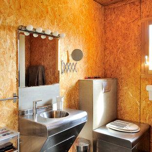 Diseño de cuarto de baño industrial, de tamaño medio, con lavabo suspendido, encimera de acero inoxidable, paredes marrones y sanitario de una pieza