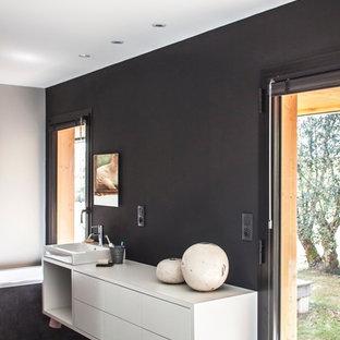 Cette image montre une grand salle de bain principale design avec des portes de placard blanches, un mur noir et une vasque.