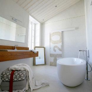 Cette image montre une salle de bain principale marine de taille moyenne avec un mur blanc, un lavabo posé, un plan de toilette en bois et un bain japonais.